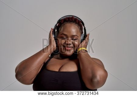 Plump, Plus Size African American Woman In Sportswear And Headphones Listening To Music Standing In