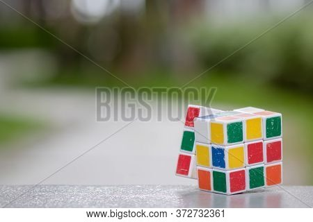 Chon Buri, Thailand - April 18, 2020: Rubik\\\'s Cube Placed On A Desk And A Green Natural Backgroun