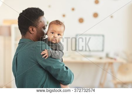 Back View Portrait Of African-american Man Holding Cute Mixed-race Baby Looking At Camera While Posi