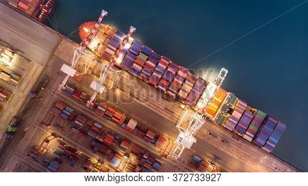 Cargo Container Ship At The Cargo International Yard Port And Crane Loading Tank For Export Freight