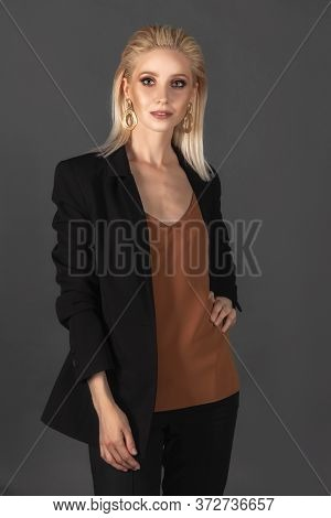 Beautiful Girl With Long Blond Hair In An Elegant Black Suit Standing Against The Dark Gray Backgrou