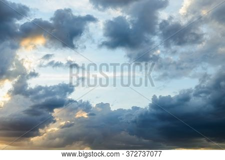 Bright Blue Sky Is Visible Through The Gap In The Dark Clouds At Evening. Rain Clouds Surround The L