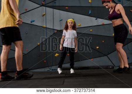 Active Woman And Little Girl Going To Climb, Male Instructor Helping Them To Warm Up Against Artific
