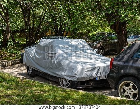 Varna, Bulgaria, June 18, 2020. Silver Weatherproof Cover On A Stationary Car Parked Outdoors. Moder