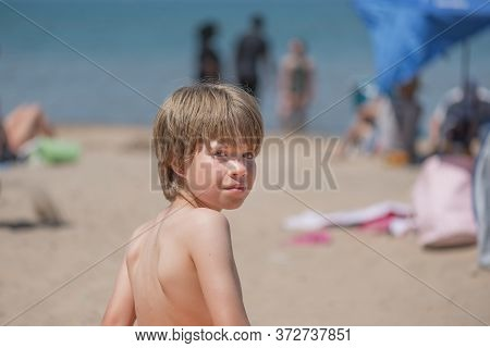Portrait Of A Handsome Boy Sitting On A Beach, Looking At The Camera From The Back