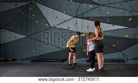 Active Little Girl Going To Climb, Male And Female Instructor Helping Kid, Standing Against Artifici