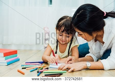Happy Asian Child Kid Daughter Kindergarten And Young Beautiful Parent Mother Teaching Drawing And P