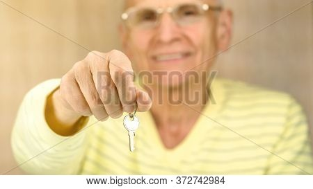 Blurry Smiling Aged Man In Glasses And Yellow Pullover Holds Key To Door In Hand Against Brown Woode