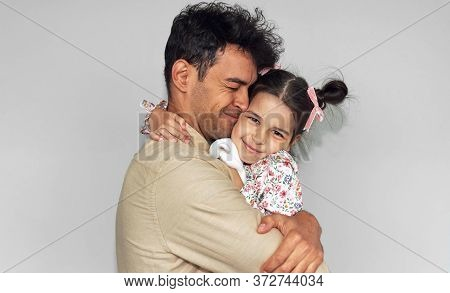 Loving Father Hugging His Daughter Against The Gray Wall. Happy Child And Daddy Feeling Joyful. Hand