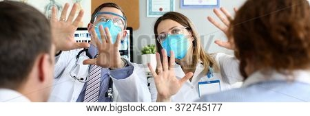 Portrait Of Medical Workers Wearing Face Masks. Woman And Man Co-workers Surprised On Hospital Appoi