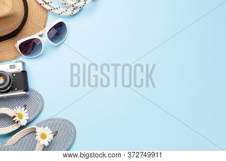 Summer vacation items and accessories. Flip flops, sunglasses, camera and sun hat on blue background. Top view flat lay with copy space