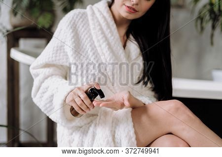 Cropped View Of Young Adult Woman Using Care Cosmetic Product In Glass Bottle With Natural Pampering