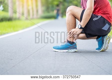 Young Adult Male With His Muscle Pain During Running. Runner Man Having Leg Ache Due To Ankle Sprain