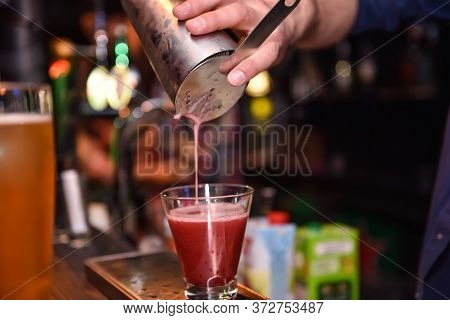 Bartender Pours A Cocktail Into A Glass At Bar Counter.