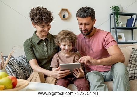 Cute little boy with touchpad and his young affectionate parents watching online video or movie or searching for curious cartoons in the net