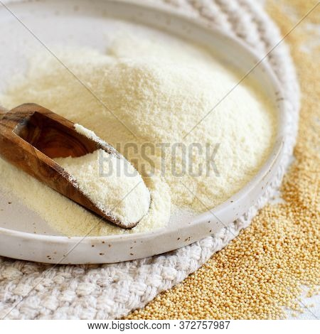 Plate Of Raw Amaranth Flour With A Spoon And Amaranth Seeds Close Up