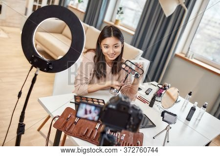 Asian Female Blogger Showing Cosmetic Products While Recording A Tutorial Video For Her Beauty Blog
