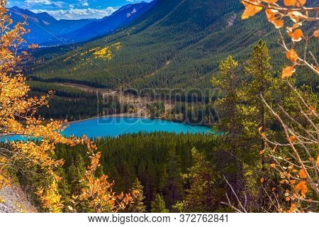 The azure icy water of the Kananaskis River in the mountain valley of Peter Lougheed Provincial Park. Lush autumn in the Canadian Rockies. The concept of active, ecological and photo tourism