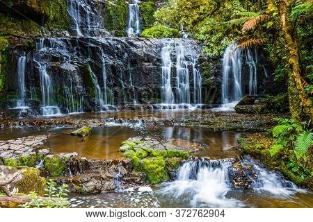 New Zealand, South Island. Picturesque multi-tiered cascading waterfalls among the green forest. Purakaunui Falls. The concept of active, environmental and photo tourism