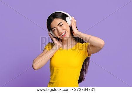 Wireless Headphones For Music. Portrait Of Happy Asian Girl Enjoying Listening Favorite Songs, Posin