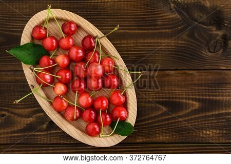 Sweet Red Cherries In An Oval Wooden Bowl On A Wooden Table With Copy Space For Text. Top View.