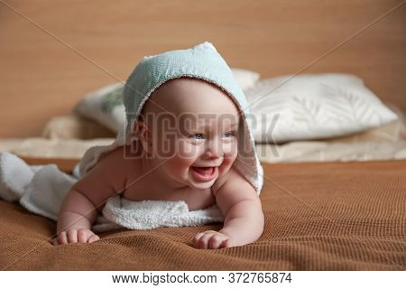 Ute Little Baby Lies On Bed Wrapped In White Towel With Hood