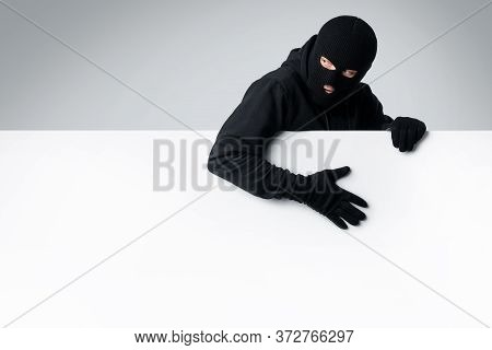 Masked Gangster Holding White Blank Advertising Panel And Looking Back, Isolated Over White Studio W