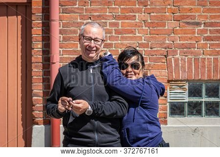 A Middle Aged (50+) Racially Mixed Couple  (caucasian And Asian) Enjoy Outing Together. Red Brick Wa