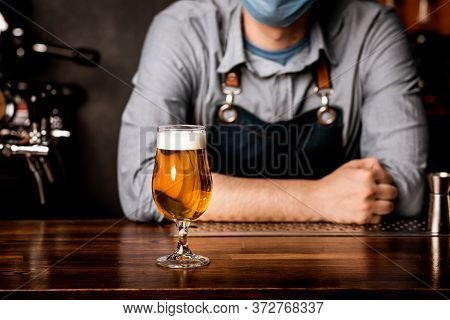 Quarantine, Nightlife And Pub. Bartender In Protective Mask Leans On Bar Counter On Which Stands Gla