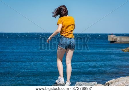 Malmö, Sweden - June 14, 2020: A Young Girl Balance On A Stone, Looking At The Blue, Cold Waters Of