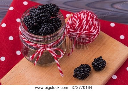 Glass Jar Overfilled With Blackberries. Knot On A Jar. Red Dotted Background.