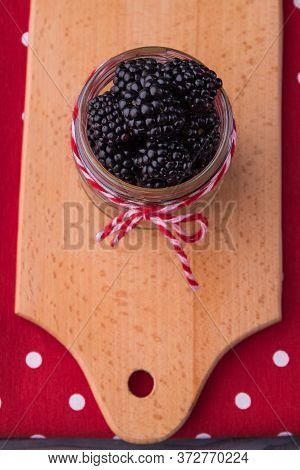 Knotted Jar, Black And White Thread. Top View. Overfilled With Blackberries, Wooden Board Background