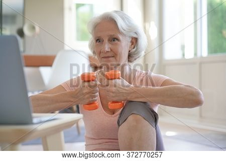 Senior woman doing fitness exercises with virtual class, holding dumbbells