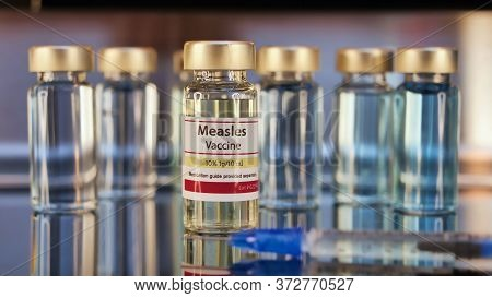 Vial Of Measles Vaccine And Syringe Stainless Steel Background