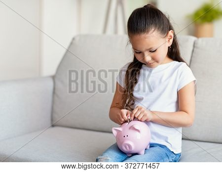 Personal Savings. Little Girl Putting Coin In Piggybank Sitting On Sofa At Home. Copy Space