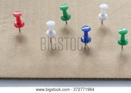 Multi Colored Push Pins On White Cardboard Paper Texture Background. Pushpins Collection.