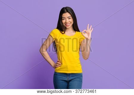 All Is Ok. Joyful Asian Girl Showing Okay Sign Gesture And Smiling, Posing Over Purple Studio Backgr