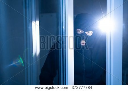 Robbery Concept. Aware Masked Villain Lurking Into House Through Window Or Glass Door, Using Torch I
