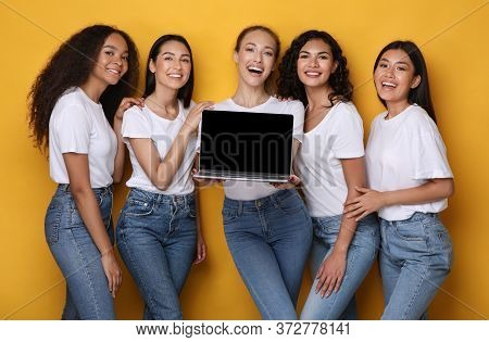 Five Multiethnic Women Holding Laptop Showing Blank Computer Screen Recommending Girlish Website Sta