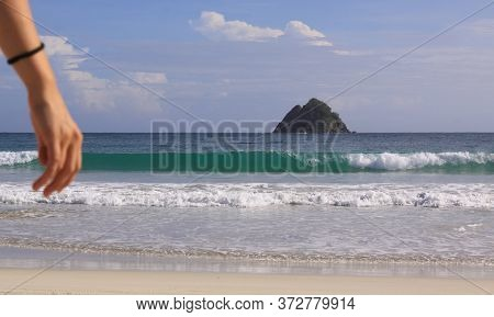 Hand Of Woman And Wave Background At Mawun Beach. Kuta Lombok Is An Exotic Paradise On The Indonesia
