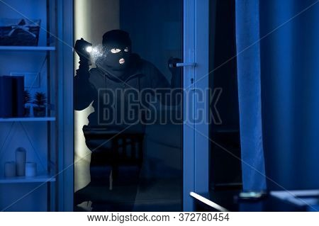 Vandalism Concept. Disguised Villain With Torch Watching Enclosed Property Through Balcony Glass Doo