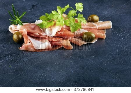 Italian Prosciutto Crudo Or Jamon With Rosemary. Raw Ham Appetizer On Table
