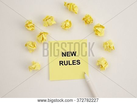 Text New Rules Written On Yellow Note Paper On White Table With Wrinkled Papers Around. New Rules Co
