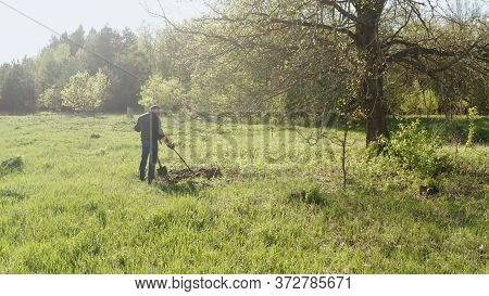 A Man Is Looking For Metal With A Metal Detector. A Guy With A Metal Detector Is Looking For A Treas