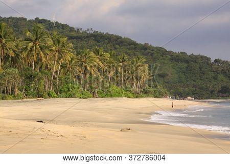 One Person Alone On Empty Beach At Pantai Setagi, Near Senggigi, Lombok, Indonesia. Exotic Tropical