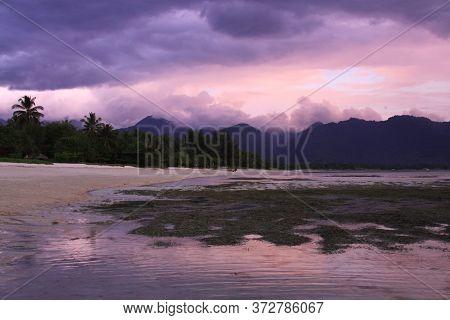 Beautiful Purple Sunset Colors Pantai Sejuk Pundewa Beach. Exotic Tropical Destination Beach On Isla