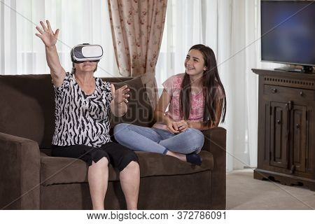 Senior Woman With Virtual Reality Headset Or 3d Glasses Having Fun With Her Granddaughter. People Ha