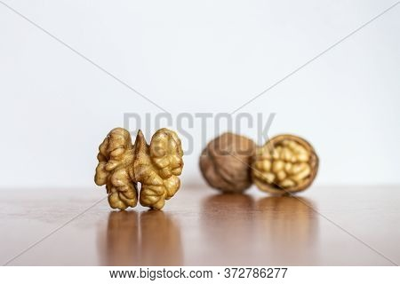 Walnut Kernel, Halves Against The Background Of Other Walnut Kernels Close Up Macro. A Walnut Is The