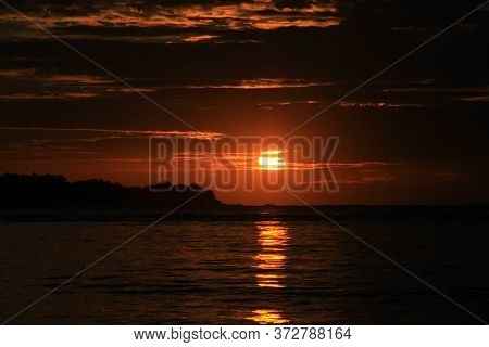 Deep Red Sunset With Sun Going Down From Behind Clouds And Light Reflection On Water Surface, On Tro