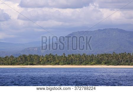 Exotic Sandy Beach In Tropical Landscape With Palm Trees And Mountains In Background, On Gili Air Is